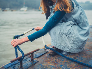 Young woman tying rope on jetty