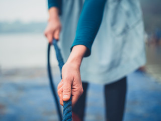 Young woman pulling a rope on a jetty