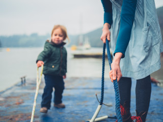 Mother and toddler pulling rope on jetty