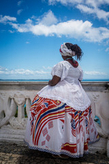 Woman dressed in a traditional clothes of  Baiana looking at the sea over a balustrade, Salvador, Bahia, Brazil