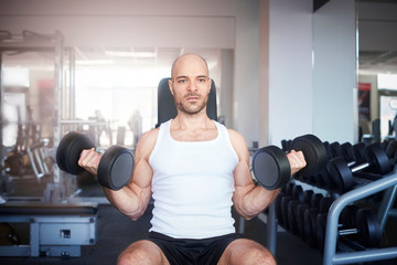 Man using dumbbell while workout in the gym