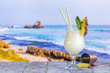 Cold pina colada cocktail in a glass on the beach with seascape background