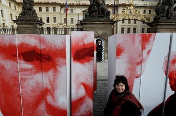 A woman poses next to a paper wall during a flash mob event in Prague