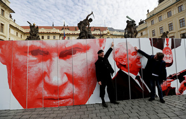 People pose in front of a paper wall during a flash mob event in front of Prague Castle in Prague