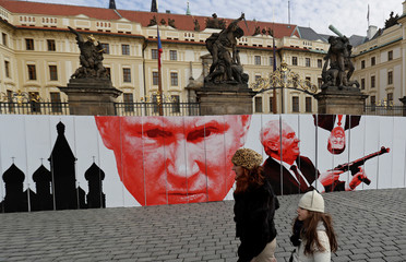 People walk past at a paper wall during a flash mob event in Prague
