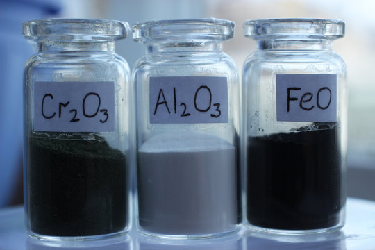 Metal oxides in glass jars: dark green chromium oxide, white aluminium oxide, black iron oxide.
