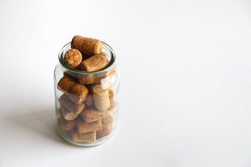 Wine corks lie in a glass jar on a white background.