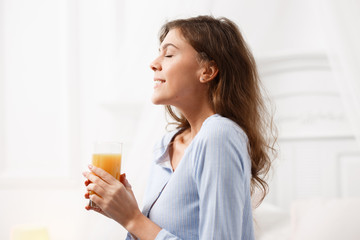 Happy brunette girl dressed in the light-blue pajama holds a glass of fresh juice in her hands and smiles in the cozy light room