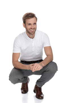 crouched casual man smiles and holds palms together