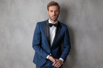 Elegant man wearing a blue tuxedo holding hands