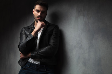 attractive man in leather jacket with finger on his chin