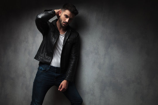fashion man in leather jacket posing with hand behind  head