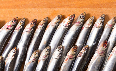 Salted European anchovies on wooden surface