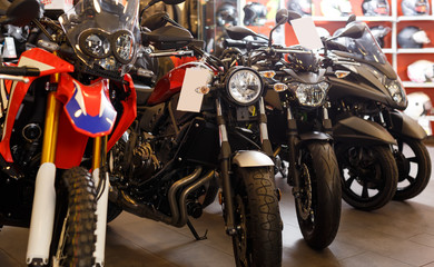 View of range new motorcycles parked in showroom for sale