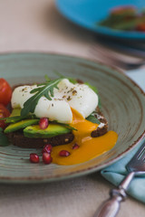 sandwich with avocado, poached egg, arugula and cherry tomatoes