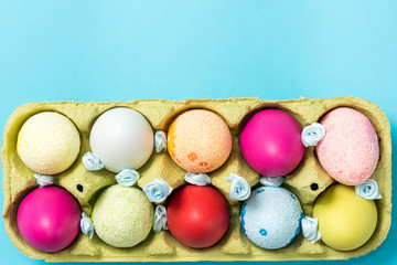 Easter eggs are painted in bright colors, lie in a cardboard eco-packaging. Blue background. Easter ideas. Space for text. Egg eco tray. Happy easter.