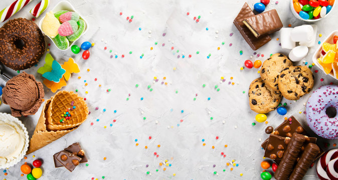 Selection of colorful sweets - chocolate, donuts, cookies, lollipops, ice cream top view