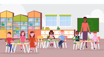 woman teacher teaching mix race boys and girls preschool modern kindergarten children classroom with chalkboard desks chairs kid room interior full length flat horizontal