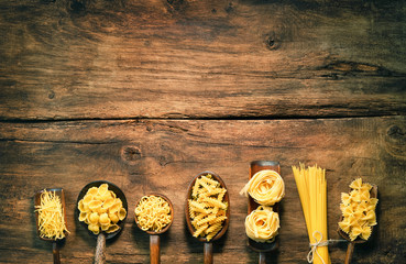 Various pasta on spoons over wooden background