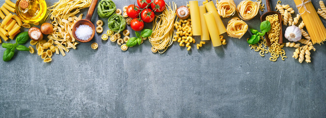 Various pasta over stone background