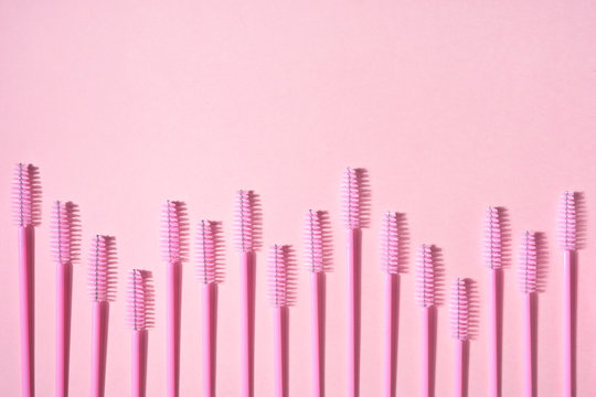 Creative concept beauty photo of lashes extensions brush on pink background.