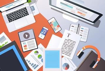 digital content management information technology concept top angle view desktop computer tablet laptop smartphone article text document office stuff horizontal