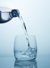 Clean drinking water flows from the bottle into a clear glass with beautiful bubbles.