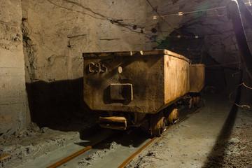 Underground gold ore mine shaft tunnel gallery passage with wagon