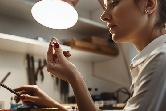 Perfection. Close up of young female jeweler looking and inspecting a ring.