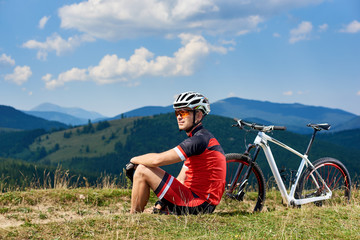Young sportsman cyclist in professional sportswear and helmet sitting near his bicycle on grassy roadside, resting and enjoying mountain view on sunny day. Active lifestyle and outdoor sport concept