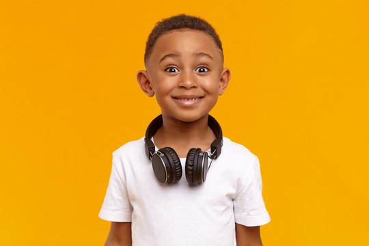 Positive human facial expressions, emotions and reaction. Isolated image of emotional handsome black schoolboy wearing white top and wireless headset around his neck, being amazed or excited
