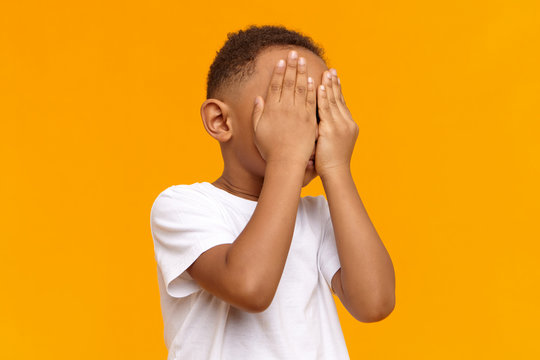 Human emotions, reaction and body language. Unrecognizable black child playing hide and seek. Dark skinned African boy covering face with both hands, feeling scared, ashamed or hiding tears