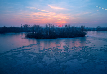 Aerial view of an island with cormorant nest colony on a frozen lake after sunset. Red clouds in the sky and on the ice.  Winter nature of Central Europe. Beauty of Czech republic.