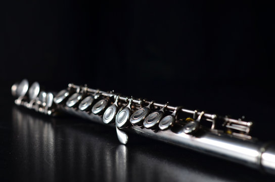 Glossy silver transverse flute on a black background