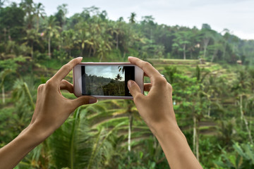 Woman shooting photo on terraced rice fields background on Bali
