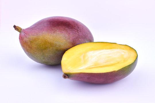 Whole and half of ripe mango. Ripe mango fruit on light background. Juicy exotic fruit.