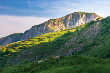 beautiful landscape of romania mountains. springtime nature at sunrise. distant cliff in morning light