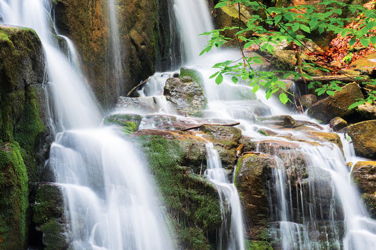 waterfall with small cascades. beautiful nature background in summer. branch with green leaves above. long exposure