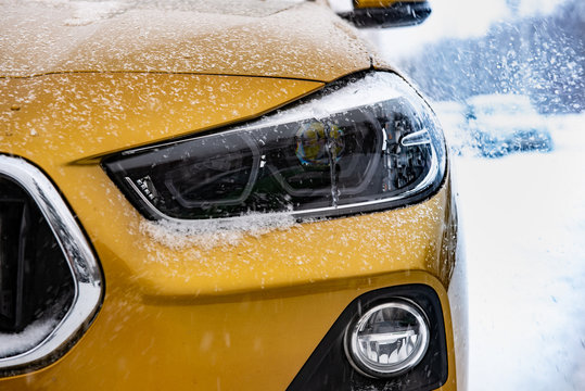 The image in front of the yellow SUV car scene behind as the sun going up with snowflakes in the right