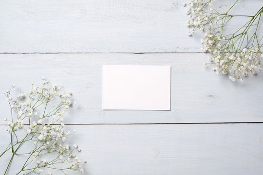 Blank card on blue wooden desk with flowers. Empty greeting card for your congratulation with Easter, Mother or Womans day, spring background,