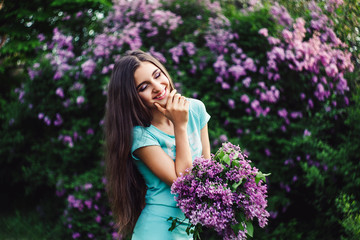 Wonderful spring. Cute young girl enjoys nature among the blossoming lilac and holds a bouquet.