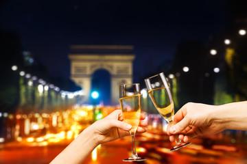 Paris arc de triumph with glasses of champagne