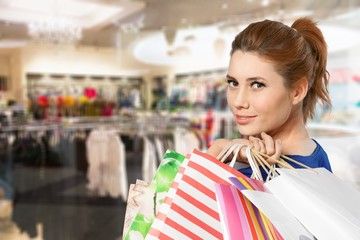 Young woman with shopping bags on blurred shopping mall background