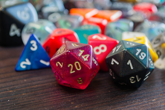 various colorful polyhedral game dice on a table with a 20 and a one in the foreground