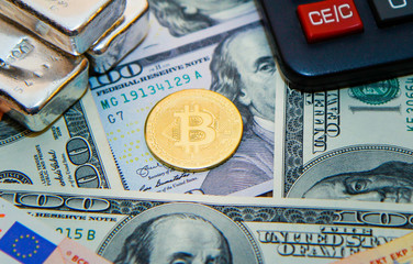 Bitcoin gold coin on a background of paper dollars and euros