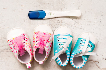 Baby booties pink and blue on a light background next to a positive pregnancy test. Ivf pregnancy concept.