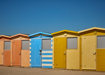 Row of colorful wooden bathing huts (changing rooms) in the beach