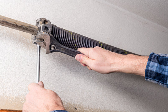 Home repairman uses tools to work on a garage door spring