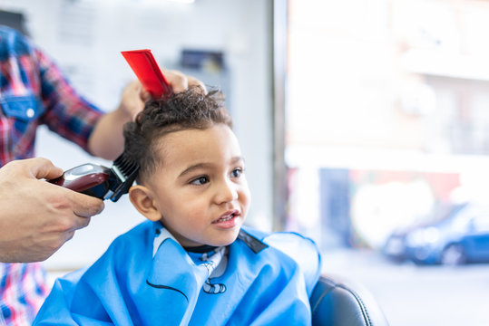 Cute Boy Getting a Hair Cut in a Barber Shop. Beauty Concept.