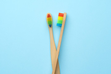 Photo of two wooden toothbrushes with rainbow-colored bristles .